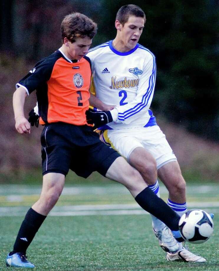 Ridgefield's Joseph DeVivo and Newtown's Joshua Barrett shove to get the ball during a Class LL state tournament, first round boys soccer game held Treadwell Town Park. Monday, Nov. 8, 2010 Photo: Scott Mullin / The News-Times Freelance