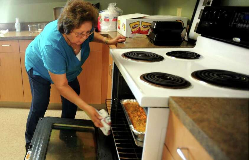 Betty Adkins warms up a cassarole dish before the community pot luck fellowship gathering sponsored