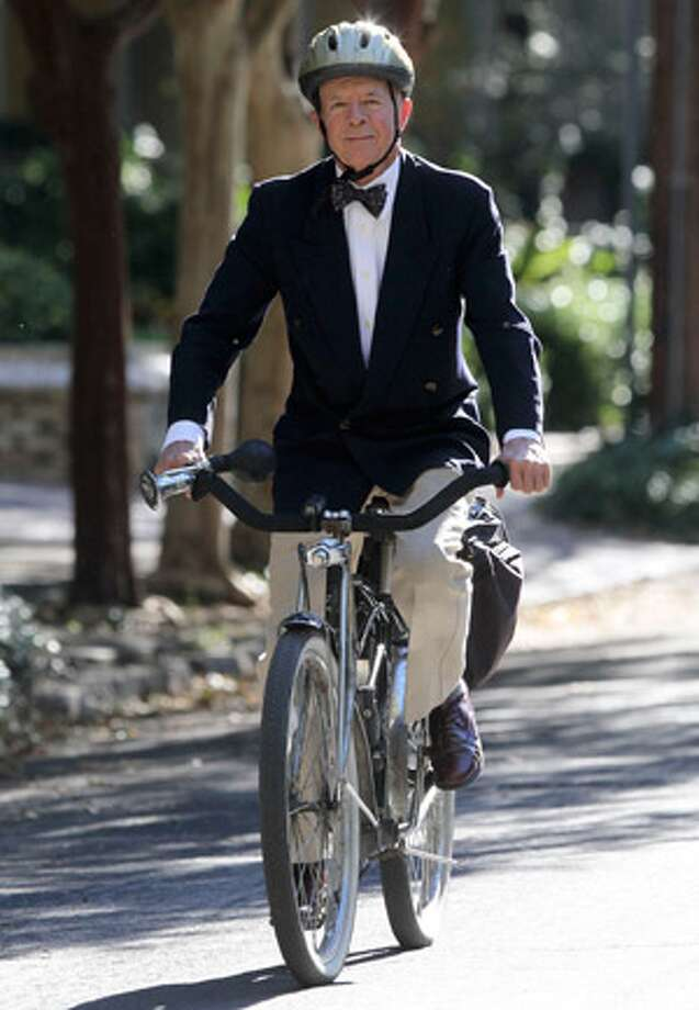 San Antonio attorney Mike Casey rides his bicycle through the King William neighborhood. Casey used to wear this hat when riding his bicycle but has changed to a helmet after the recent death of artist Chuck Ramirez.