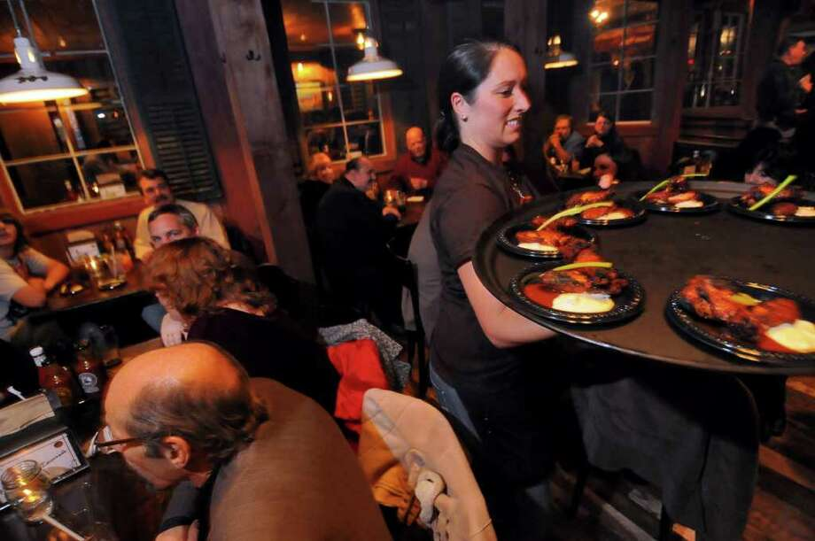 "Server Nikki Bates brings chicken wings appetizers to visitors during a ""sneak peek"" of the new Dinosaur Bar B Que in Troy,  on  Monday evening. ( Philip Kamrass / Times Union ) Photo: Philip Kamrass"