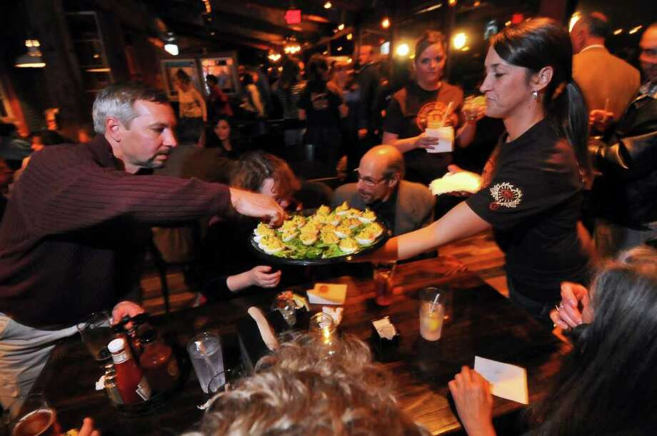 "Server Nikki Bates serves a Creole deviled eggs appetizer to visitors during a ""sneak peek"" of the new Dinosaur Bar B Que in Troy, on  Monday evening.   ( Philip Kamrass / Times Union ) Photo: Philip Kamrass"