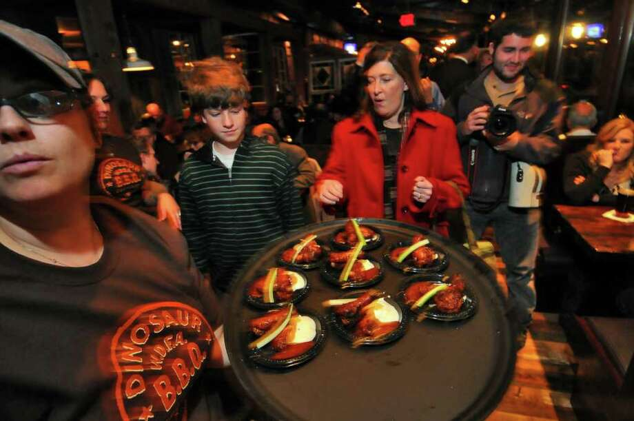 "Server Maria Dziamba, left,  brings chicken wings appetizers to visitors during a ""sneak peek"" of the new Dinosaur Bar B Que in Troy,  on  Monday evening.   ( Philip Kamrass / Times Union ) Photo: Philip Kamrass"