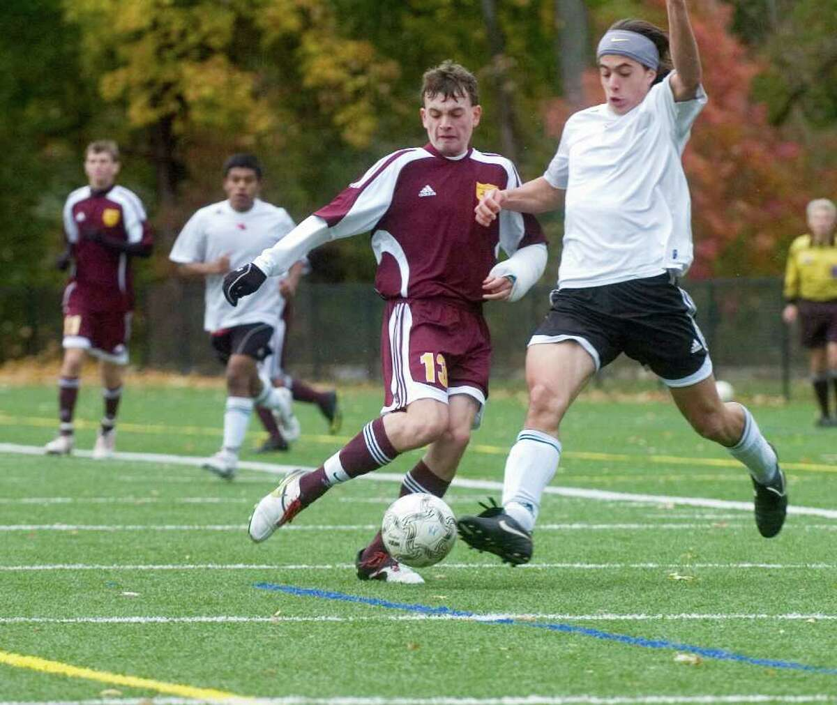 South Windsor High School's # 13, Evan Cheman, left, fights with Greenwich High School's #18, Phillip Collins in the first round of the Class LL boys soccer tournament hosted by Greenwich, on Monday, Nov. 8, 2010.