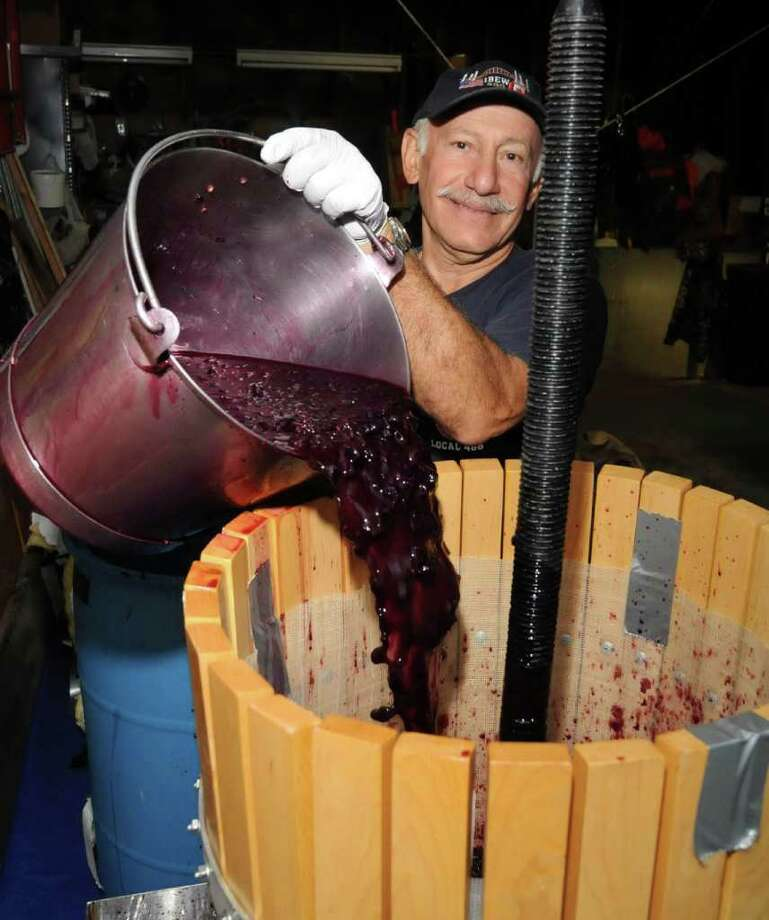 George Chaber, of Brookfield, loves to make his own wine each fall. Here he pours his crushed formented grapes into the wine press. Fri. Oct. 1, 2010. Photo: Lisa Weir / The News-Times Freelance