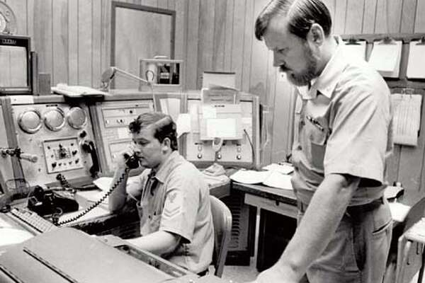 Sabine Coast Guard Station commanding officer, Lt. Cmdr. Frank Peasley, right, and radioman Ronald Brasher constituted half of the crew manning the station Tuesday, keepign tabs on Delia.