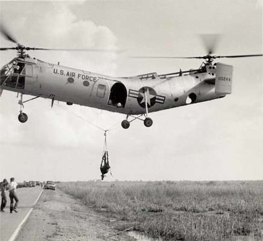 "A helicopter is bringing out a cow in a net. Crews became entangled and this method was abandoned for ""tied feet upside-down"" method."