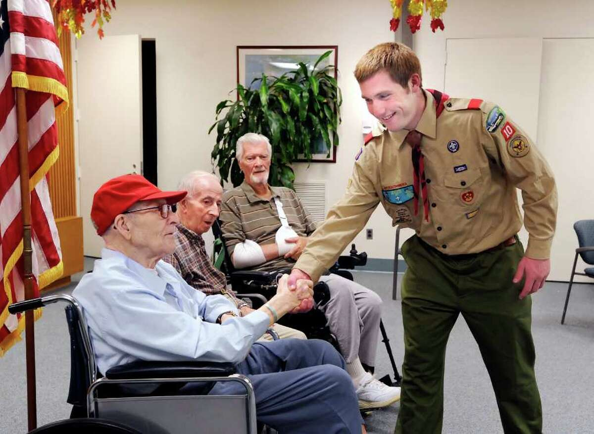 Boy Scout Francis Ambrogio, 17, of Cos Cob, right, shakes hands with World War II Marine veteran Thomas Lee, left, during a gathering at Nathaniel Witherell, Greenwich, Tuesday afternoon, Nov. 9, 2010. Ambrogio, aiming to get his Eagle Scout badge, compiled an oral history project interviewing three World War II veterans, which included Lee and fellow Nathaniel Witherell residents Frank Massaro (Army medical corps), second from left and Ken Henderson (Naval aviator), background center.