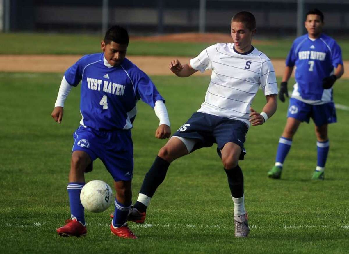 West Haven's Marco Olmedo, left, and Staples' Frankie Bergonzi, right, compete for control of the ball during Tuesday's Class LL playoff game at Staples High School on November 9, 2010.