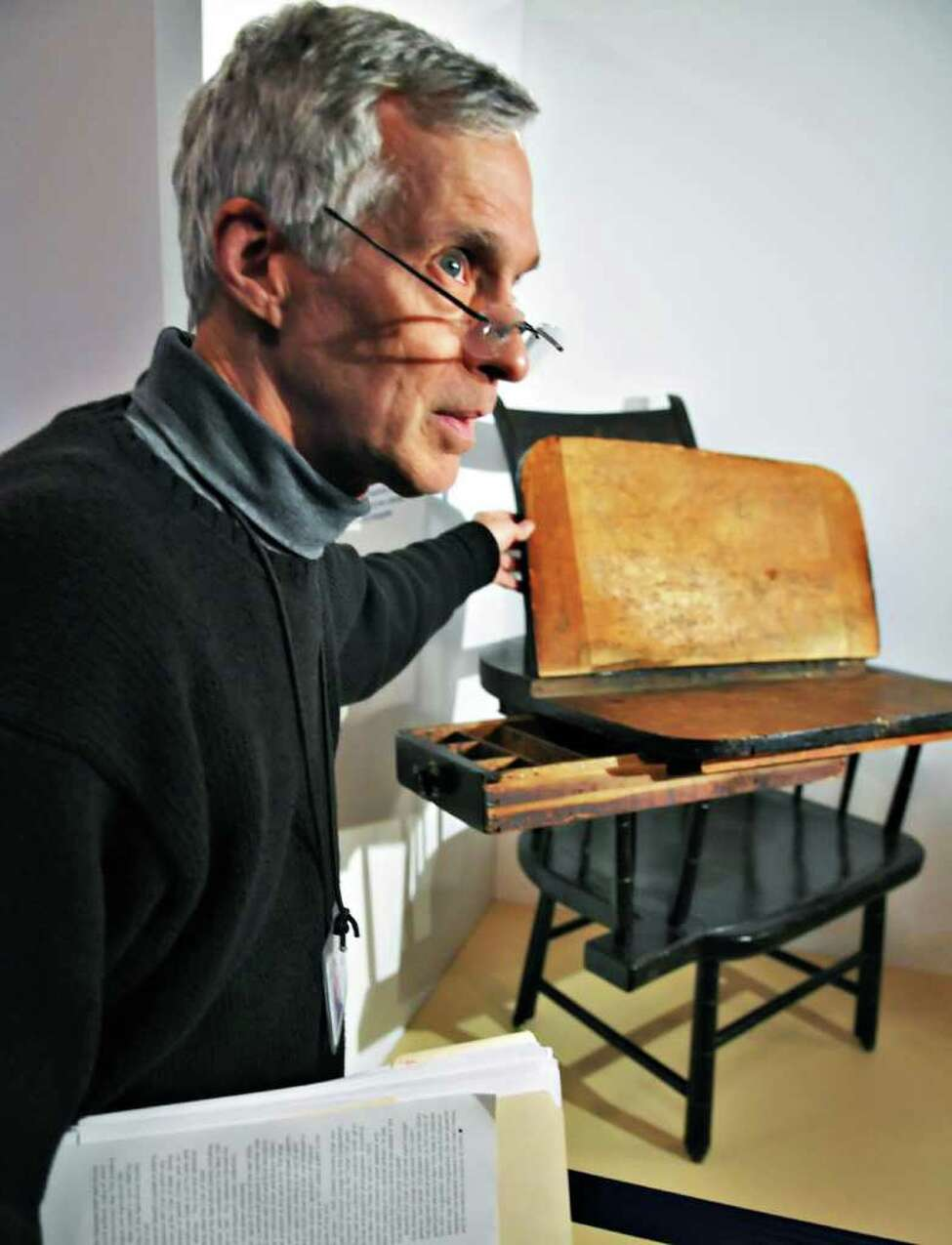 Gene Mackay, exhibit planner for the State Museum, shows graffiti on a writing chair belonging to Dewitt Clinton, part of an upcoming public display of historic artifacts at the state Capitol on Tuesday afternoon November 9, 2010. (John Carl D'Annibale / Times Union)