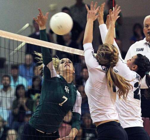 Reagan's Bailey Shurbet tries to get a shot past two Corpus Christi King defenders. King won 25-21, 25-17, 25-20, snapping the Rattlers' 26-match winning streak.