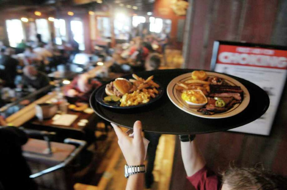 A tray of food is brought out of the kitchen  at the grand opening for the Dinosaur Bar-B-Q in Troy, on Wednesday, Nov. 10, 2010.   (Paul Buckowski / Times Union) Photo: Paul Buckowski