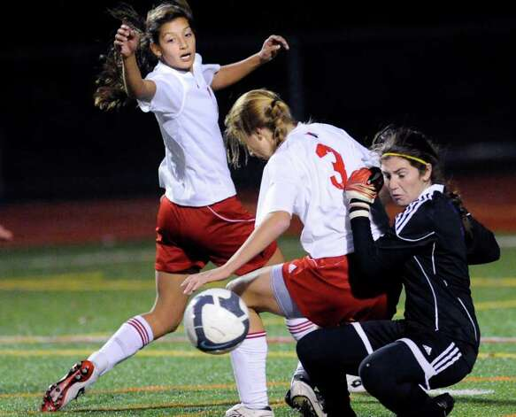 Westhill goalie, Jenn Osher, right, makes a stop as Amanda Onofrio, #3, of Greenwich High School, attempts to play the rebound during the 2010 Girls FCIAC Soccer Championship between GHS and Westhill High School. The Cardinals defeated Westhill, 1-0, in a double overtime thriller. Photo: Bob Luckey, ST / Greenwich Time