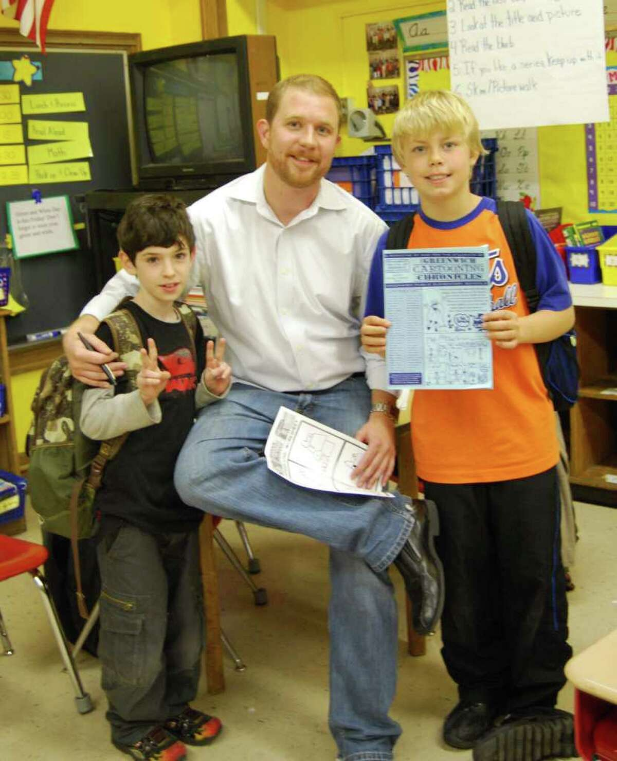 Phil Lohmeyer poses with Julian Curtiss students Tim Catalano and Gavin Muir. Muir is holding a copy of the Greenwich Cartooning Chronicles, which is produced by the students in Lohmeyer's cartooning class.