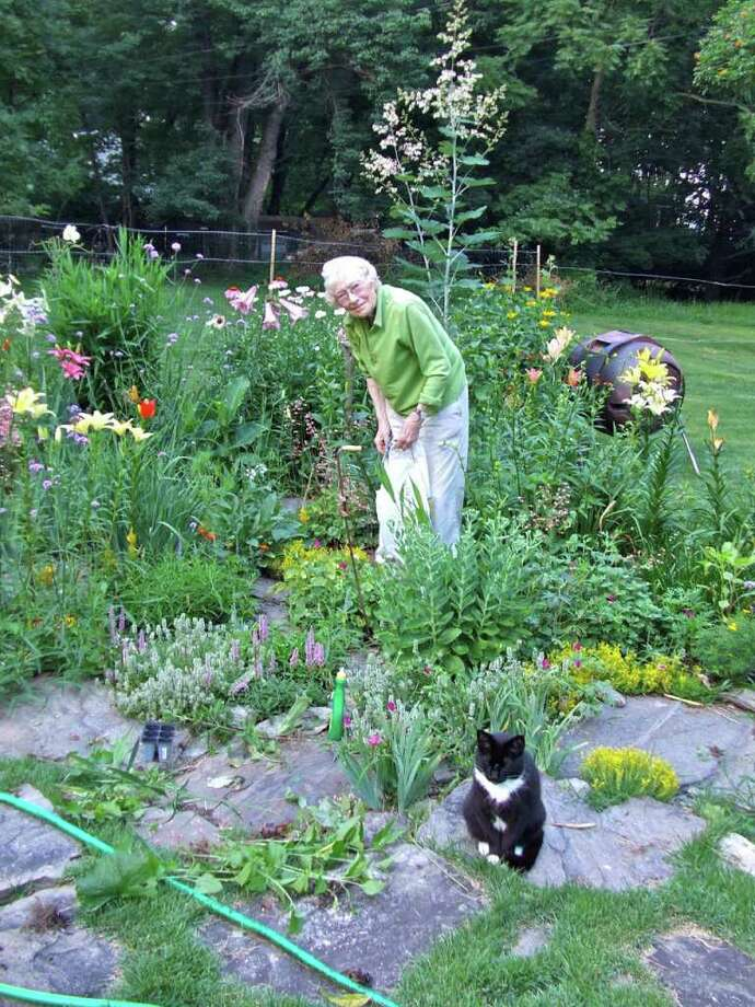 """Gabrielle """"Gay"""" Dearborn in her Wright Street garden in Westport with one of her beloved cats. Artwork by Dearborn, who died last March, encompassed a range of styles and media. Photo: Contributed Photo / Westport News contributed"""