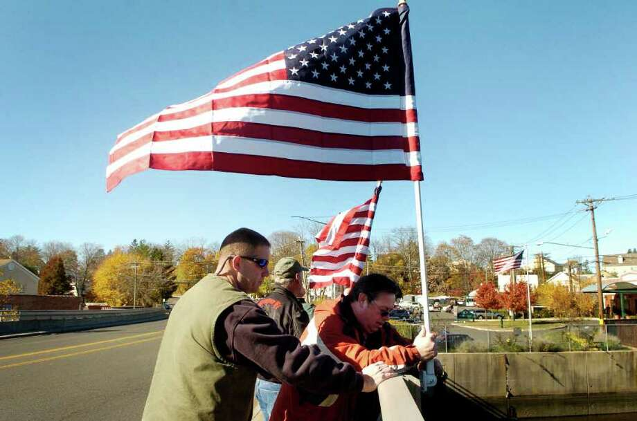 Chief John Pugni helps John Timm place flags on the Mianus River Bridge in Greenwich, Conn. on Thursday November 11, 2010. Photo: Dru Nadler / Stamford Advocate Freelance