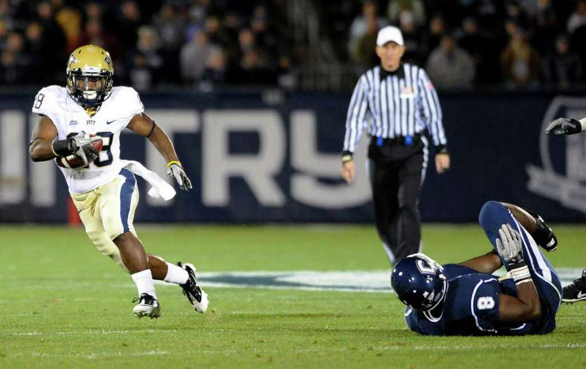 Pittsburgh's Dion Lewis, left, gets past Connecticut's Lawrence Wilson during the first half of an NCAA college football game in East Hartford, Conn., on Thursday, Nov. 11, 2010. (AP Photo/Fred Beckham)