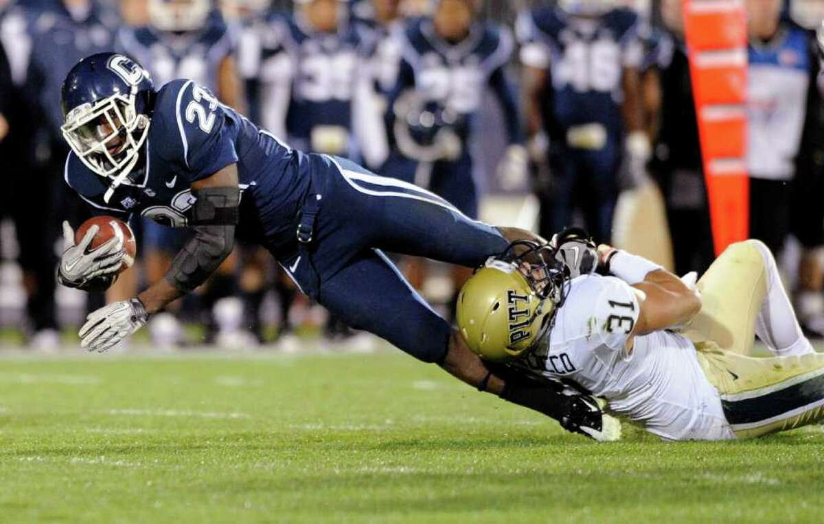 Connecticut's Jordan Todman, left, is tackled by Pittsburgh's Dom DeCicco during the first quarter of an NCAA college football game in East Hartford, Conn., on Thursday, Nov. 11, 2010. (AP Photo/Fred Beckham)