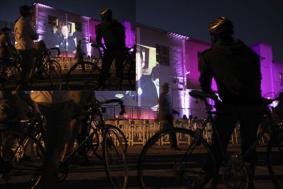 Cyclists watch a slide show of San Antonio artist Chuck Ramirez at Blue Star Art Complex.
