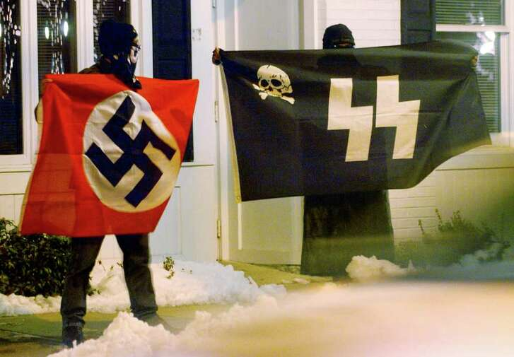 Two unidentified men claiming to be from an organization called the Imperial Klans of America hold Nazi flags to protest a menorah lighting, during an annual Hanukkah celebration on Milford Green in December 2008. The event was put together by the Chabad Jewish Center of Milford and the Hebrew Congregation of Woodmont.