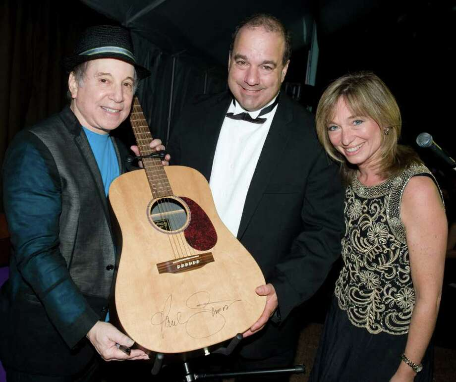 Gary Valentine, center, and his wife, Deborah, with Paul Simon, left, at Stamford Hospital's sixth annual Dream Ball charity gala Saturday. Photo: Contributed Photo / Stamford Advocate Contributed
