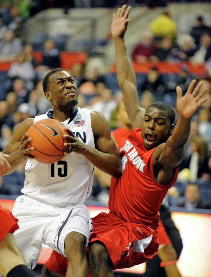 Connecticut's Kemba Walker, left, drives past Stony Brook's Anthony Jackson during the first half of their NCAA college basketball game in Storrs, Conn., on Friday, Nov. 12, 2010. (AP Photo/Fred Beckham) Photo: AP