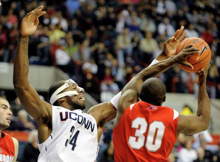 Connecticut's Alex Oriakhi (34) fights for a rebound with Stony Brook's Chris Martin during the seco