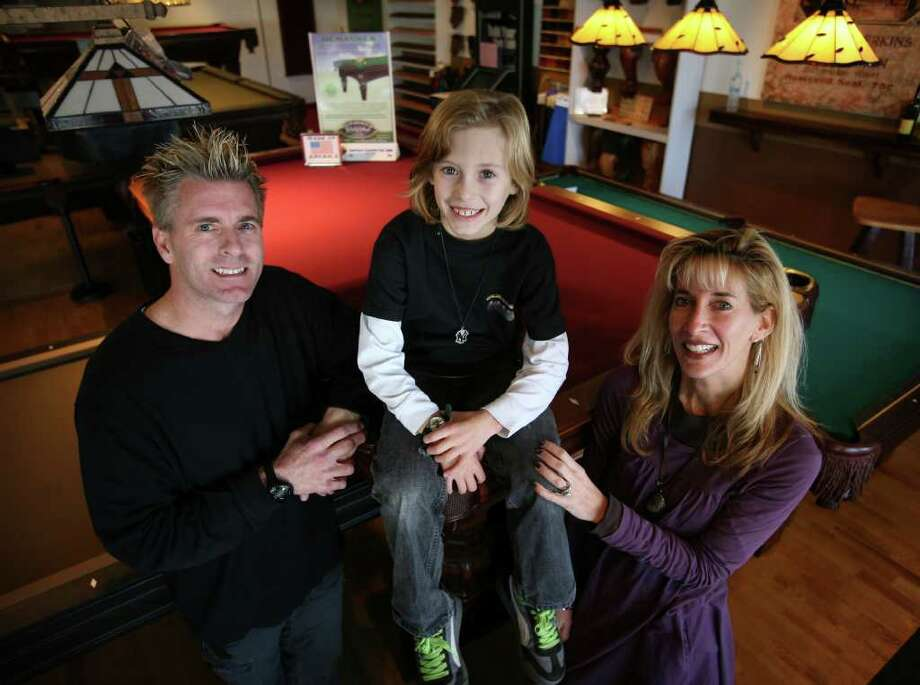 From left; David Cornwall, Jayden Cornwall, 8, and Lynne Abrams-Cornwall at Encore Billiards & Game Room at their new location at 1581 Post Road in Milford. Photo: Brian A. Pounds / Connecticut Post