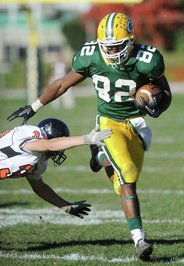 Trinity Catholic's Shawn Robinson carries the ball with pressure from  Stamford High's Greg Lupinacci in football action in Stamford, Conn. on Saturday November 13, 2010 Photo: Kathleen O'Rourke / Stamford Advocate