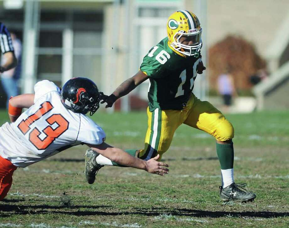 Trinity Catholic's Mike Davis carries the ball against Stamford High's Chandler Foster in football action in Stamford, Conn. on Saturday November 13, 2010 Photo: Kathleen O'Rourke / Stamford Advocate