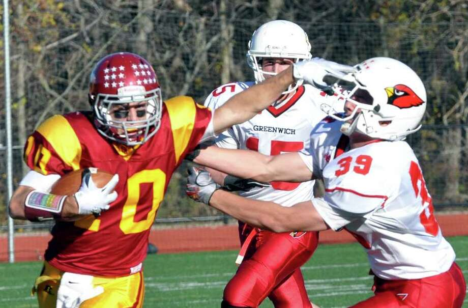St. Joseph's Pat Mulligan fends off Greenwich's Mike Daly during the football game at St. Joseph in Trumbull on Saturday, Nov. 13, 2010. Photo: Amy Mortensen / Connecticut Post Freelance