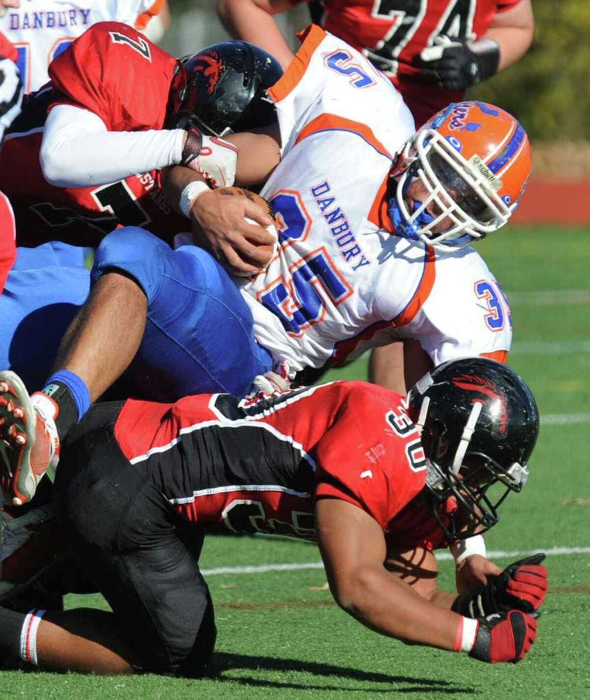 Danbury's #35 Austin Calitro, center, gets tackled by Fairfield Warde's #7 Charlie Edison, during football action in Fairfield, Conn. on Saturday November 13, 2010. On bottom is Warde's #30 Alex Delaney.