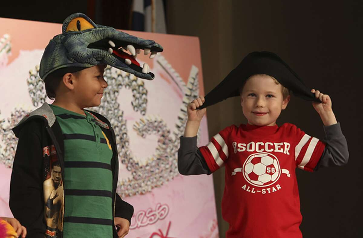 """Griffin Brooks (right), 7, fidgets with his pirate's hat as Justin Orosco, 6, wears an alligator head to help read aloud, """"Pirate Treasure Hunt!"""" by Jan Peck, at the seventh annual Express-News Children's Book & Author Celebration at Pearl Stables on Saturday."""