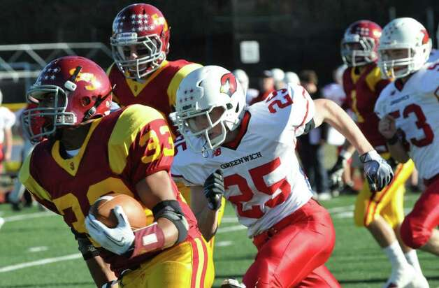 St. Joseph's L.J. Hunt carries the ball as Greenwich defender Ryan Kelly is in pursuit during the football game at St. Joseph in Trumbull on Saturday, Nov. 13, 2010. Photo: Amy Mortensen / Connecticut Post Freelance