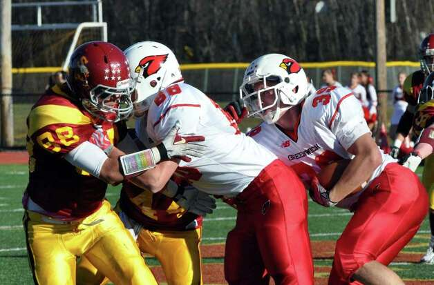 Greenwich's Mike Daly, far right, slips by with the ball as teammate Adam Milton holds off Greenwich's Quinn Irwin during the football game at St. Joseph in Trumbull on Saturday, Nov. 13, 2010. Photo: Amy Mortensen / Connecticut Post Freelance