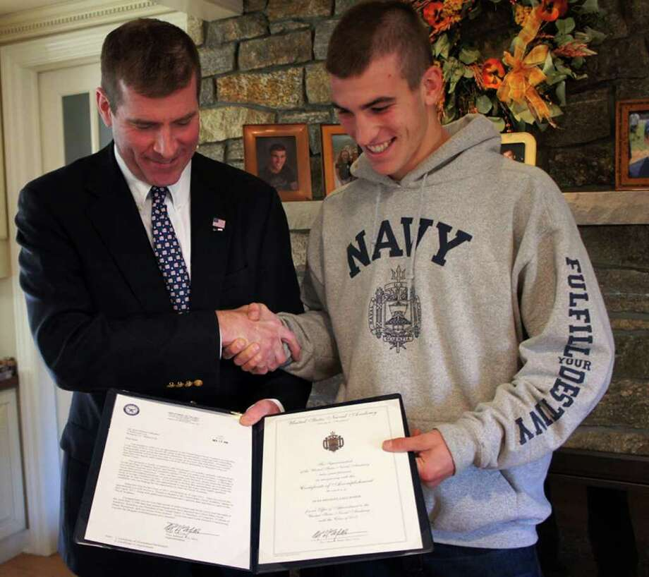 "Navy Blue and Gold Officer Jim ""Johnnieee"" Carrier presents an Offer of Appointment to Staples High School Senior Sean Gallagher at Gallagher's home on Saturday, Nov. 13, 2010. Photo: Paul Schott / Westport News"