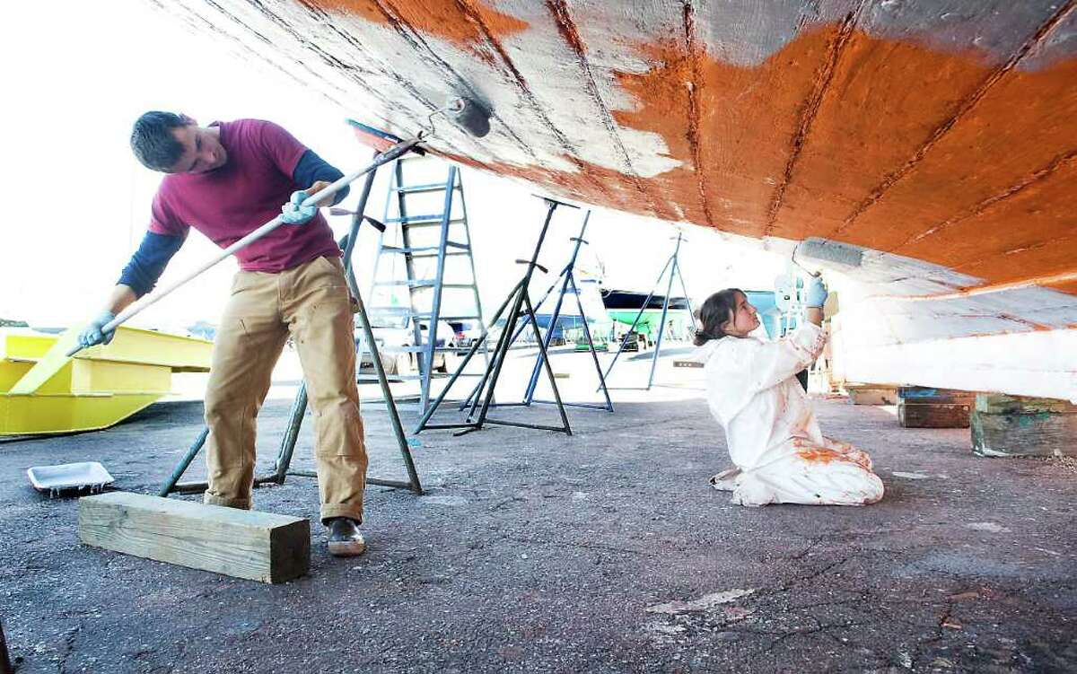 Crew members Nathan Sweard and Aubrey Gallegos apply a new coat of paint on the hull of the 106-foot long Clearwater at Norwalk Cove Marina in Norwalk, Conn. on Friday November 12, 2010.