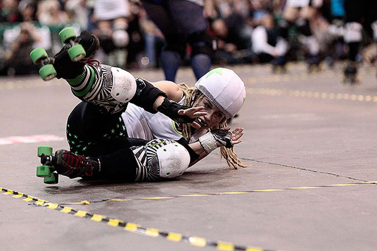 LONDON, ENGLAND - NOVEMBER 13: A competitor from the Ultraviolent Femmes goes down during the London Rollergirls Roller Derby event at London Earls Court Olympia on November 13, 2010 in London, England. The contact sport of Roller Derby involves two teams of four defensive players and one jammer, whose role it is to pass through the pack to count a score. (Photo by Matthew Lloyd/Getty Images)