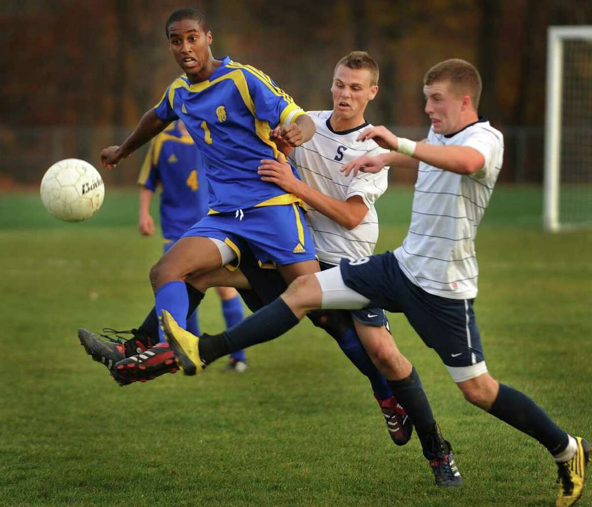 From left; Simsbury's Blake Mercer,Staples' Steven Denowitz, and Staples' Brendan Lesch play an incoming ball during the Wreckers' 1-0 victory in the Class LL quarterfinals at Staples High School in Westport on Monday, November 15, 2010.