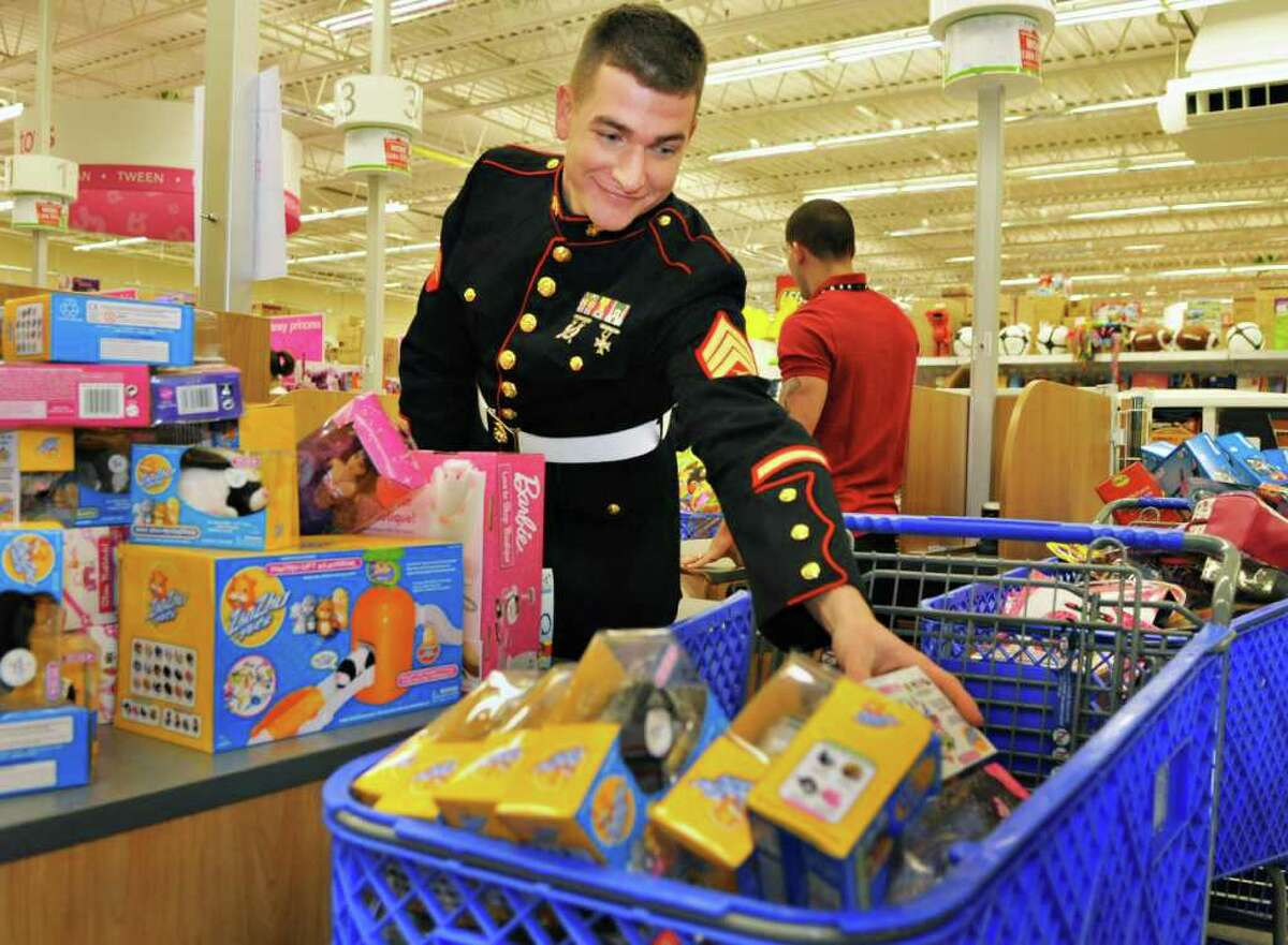 U.S. Marine Corps Sgt. Guy Bucey cashes out toys during a shopping spree with Dunkin' Donuts volunteers at Toys ?R? Us in Colonie to prepare for the Dunkin? Donuts Toys for Tots Train's annual trip throughout New York state this weekend. (John Carl D'Annibale / Times Union)