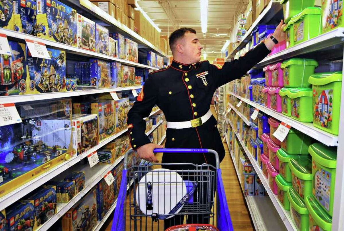 U.S. Marine Corps Cpl. Steven Flood picks out toys during a shopping spree with Dunkin' Donuts volunteers at Toys ?R? Us in Colonie to prepare for the Dunkin? Donuts Toys for Tots Train's annual trip throughout New York state this weekend. (John Carl D'Annibale / Times Union)