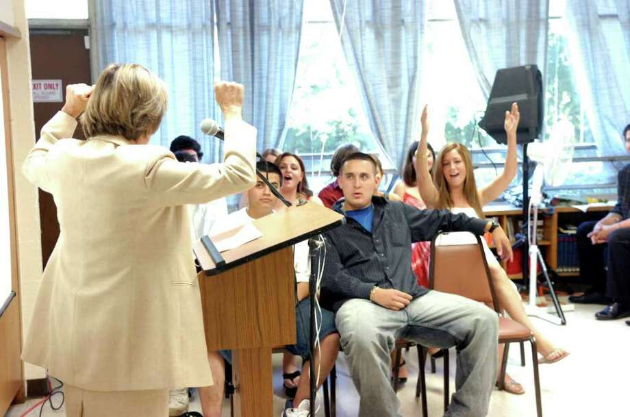 In this June 2008 file photo, Selectwoman Lin Lavery gets turns things up as she steps up to the microphone to give the commencement address during the Community Learning Program of Greenwich High School's graduation ceremony. Photo: File Photo / Greenwich Time File Photo