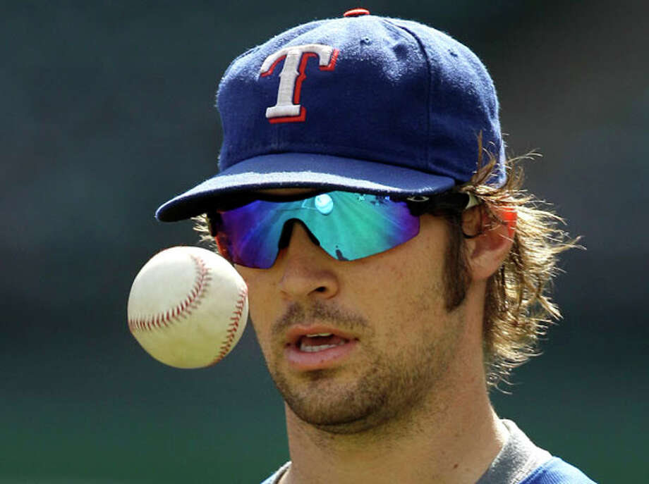 Texas Rangers starting pitcher C.J. Wilson tosses a baseball during a team practice Sunday for the World Series in Arlington, Texas. The Rangers and the San Francisco Giants are scheduled to play the opening game Wednesday. AP Photo/Tony Gutierrez / AP