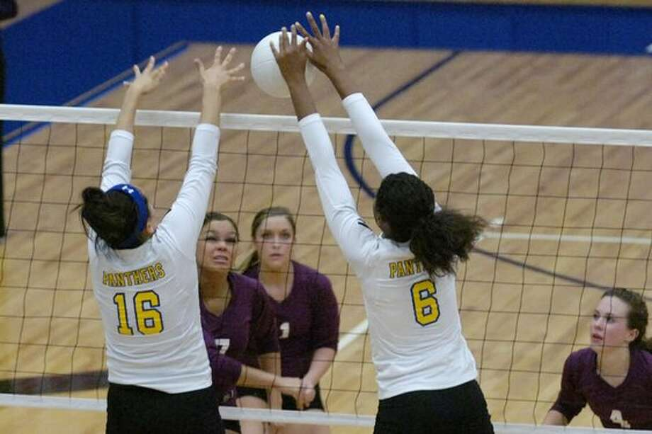 Ozen's Alexia Thomas, left, and Jerica Bolin, right attempt a block against Baytown Lee during their bi-district round of the Class 4A playoffs held at the Barbers Hill High School gymnasium in Mont Belvieu. Tuesday, November 2, 2010. Valentino Mauricio/The Enterprise / Beaumont