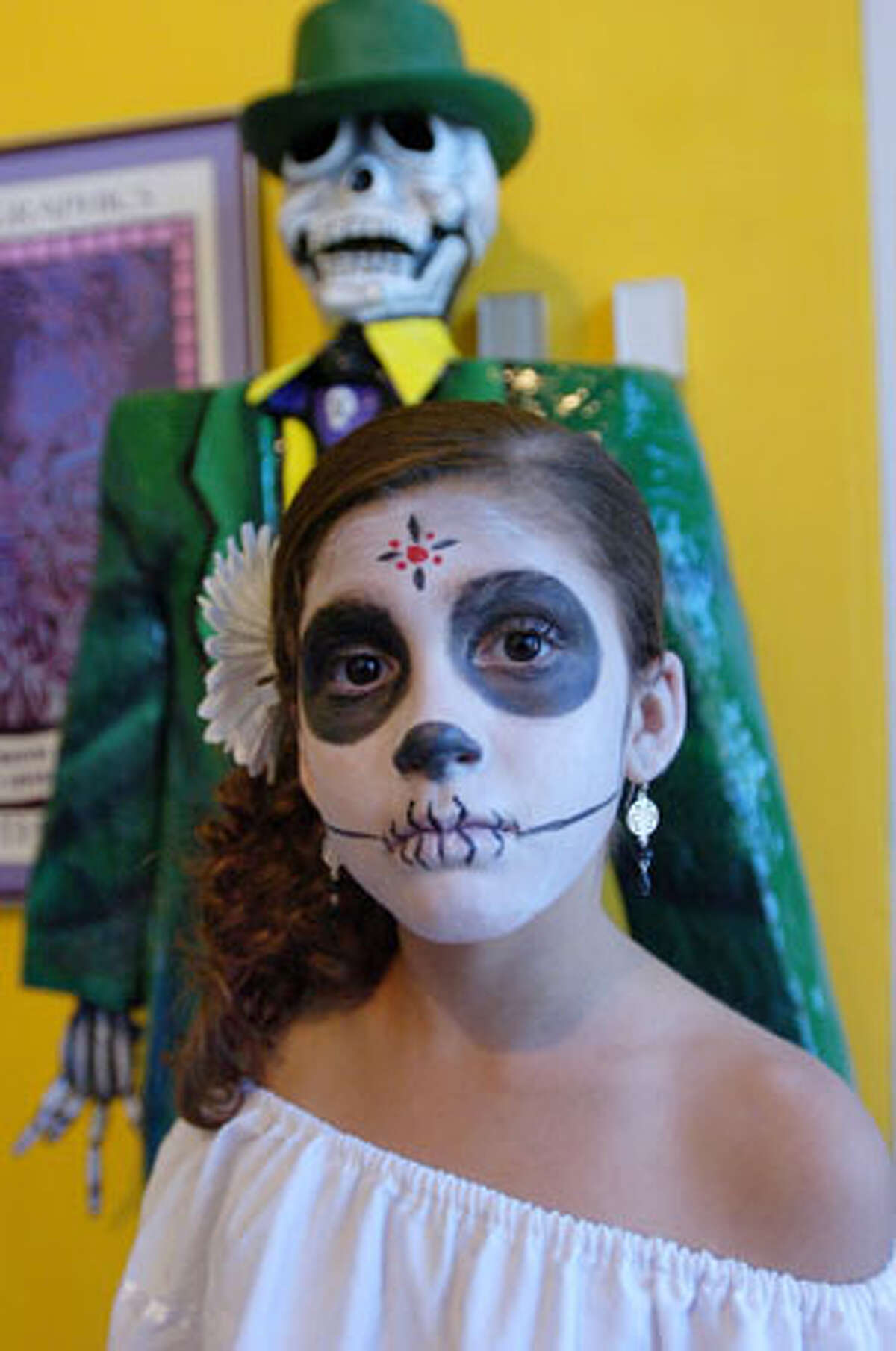 Sophia Caballero, 10, of Beaumont, stands before an ofrendas (offerings) table dressed as La Catrina during a Dia de los Muertos (Day of the Dead) event on Saturday at the Art Museum of Southeast Texas. Each year the museum, through exhibitions and hands on art projects, teaches children about the Mexican holiday and its significance in the culture. October 30, 2010. Valentino Mauricio/The Enterprise
