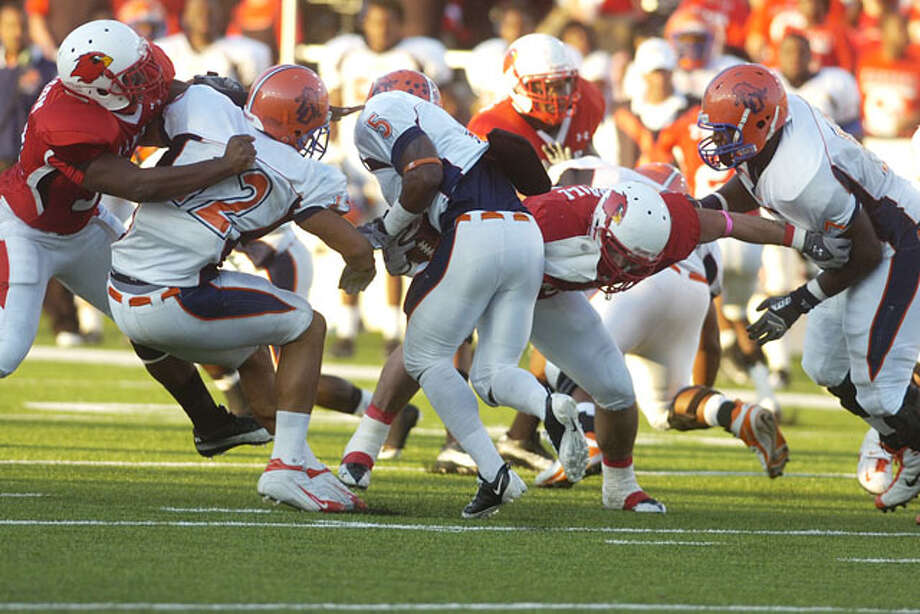 Langston University running back Carlos Ross (5) runs into a wall of Cardinals during the first half at Provost Umphrey Stadium.  Valentino Mauricio/The Enterprise / Beaumont