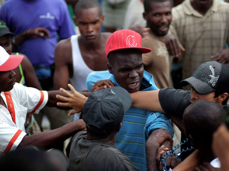 People wade through a flooded street during the passing of Hurricane Tomas in Leogane, Haiti, Friday Nov. 5, 2010. (AP Photo/Ramon Espinosa) / AP