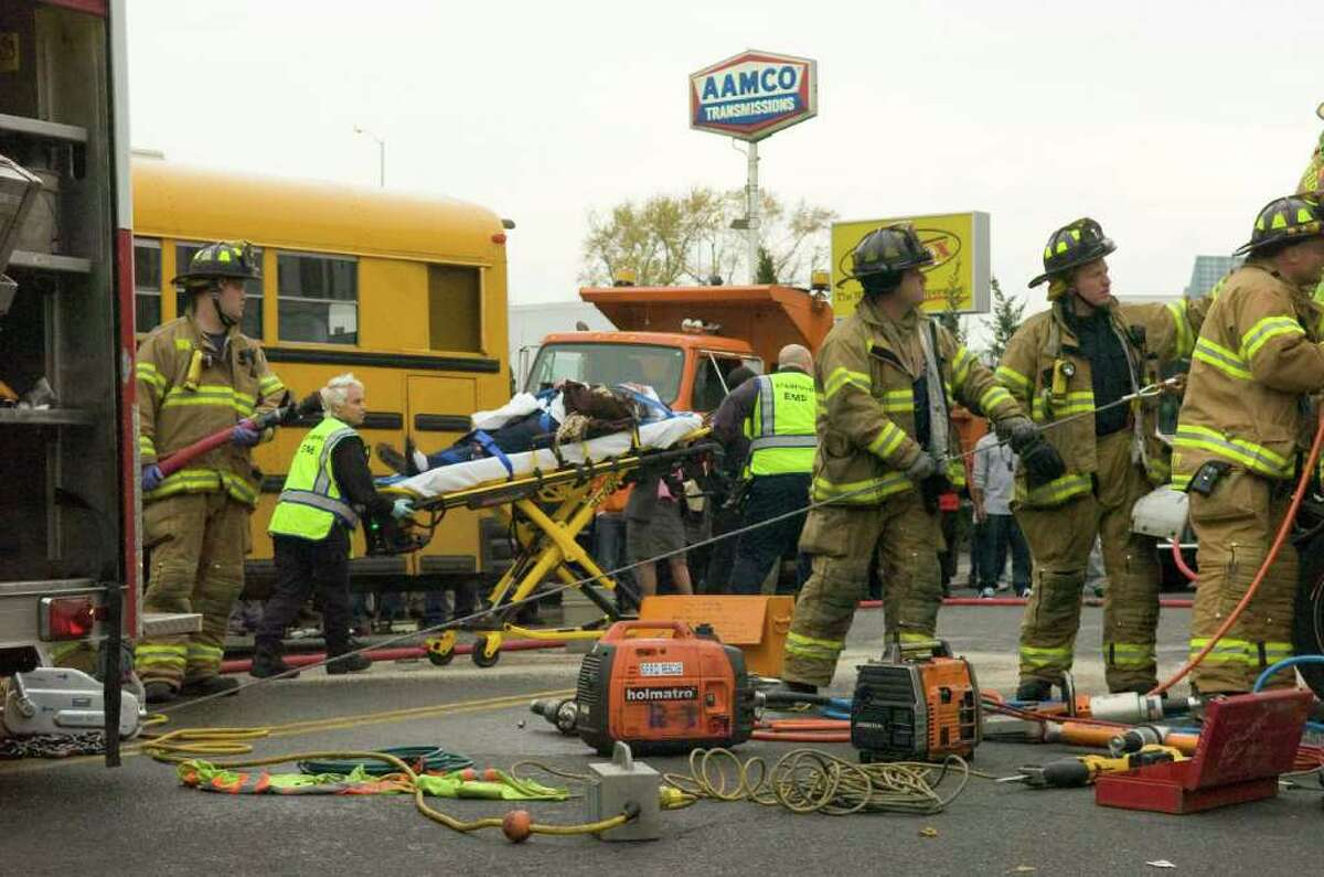 A woman is wheeled through the accident scene to an ambulance as Stamford Fire and Rescue work to extricate the driver of a box truck after a multi-vehicle accident shutting down a quarter-mile stretch of Route 1 on Stamford's East Side in Stamford, Conn., November 16, 2010. The accident occurred shortly before 2:30 p.m. when police reported a man driving erratically hit eight to nine cars, including a school bus carrying Stamford High School students.