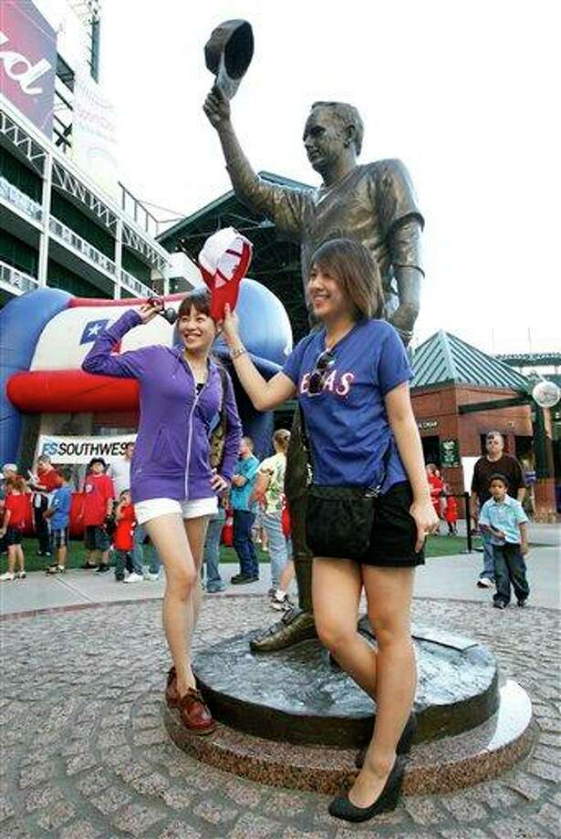 Irene Shih, left, of Taiwan, and Bella Monthawornwong, right, of Thailand, pose in front of the Nolan Ryan statue in the center field plaza before the Rangers' baseball game against the Los Angeles Angels on Saturday, Oct. 2, 2010, in Arlington, Texas. (AP Photo/Tony Gutierrez) / AP