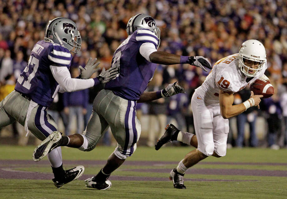 Texas kicker Justin Tucker is chased by Kansas State cornerbacks Stephen Harrison and David Garrett after losing control of the ball on a field goal attempt in the first quarter Saturday in Manhattan, Kan. (Charlie Riedel/The Associated Press)