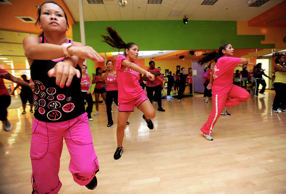 Fitness club members dance during a Party in Pink Zumbathon workout at Exygon Health and Fitness in Beaumont, Saturday. Proceeds from the event will be donated to the Susan G. Komen for the Cure. Tammy McKinley/The Enterprise / Beaumont Enterprise